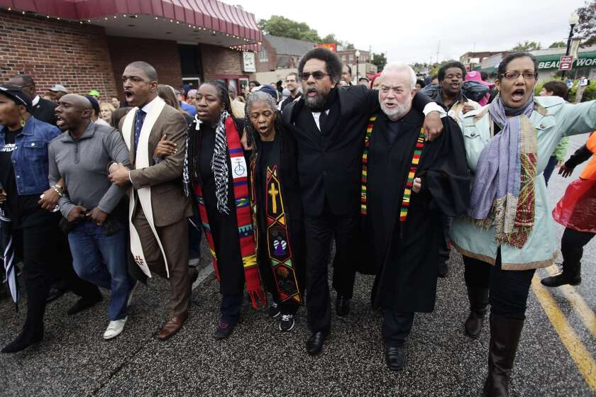Cornel West, center, joins clergy members and other demonstrators Monday to protest the shooting of Michael Brown in Ferguson, Mo.