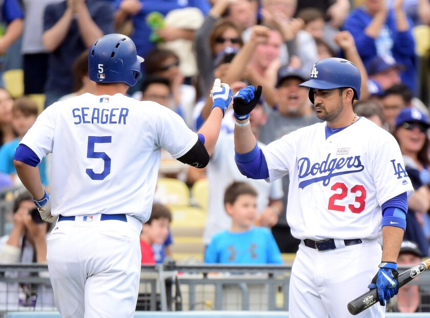 Dodgers' Corey Seager, left, celebrates his solo homerun with Adrian Gonzalez to tie the score 1-1 with the St. Louis Cardinals during the third inning.