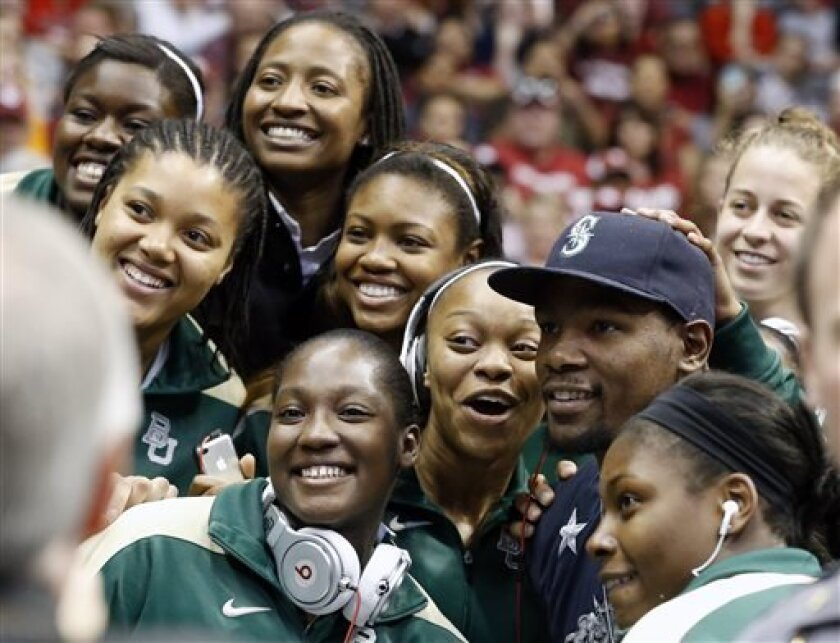 Oklahoma City Thunder NBA basketball player Kevin Durant poses for photos with Baylor players during a timeout in the second half of a regional semifinal game between Oklahoma and Tennessee in the women's NCAA college basketball tournament in Oklahoma City, Sunday, March 31, 2013. Tennessee won 74-