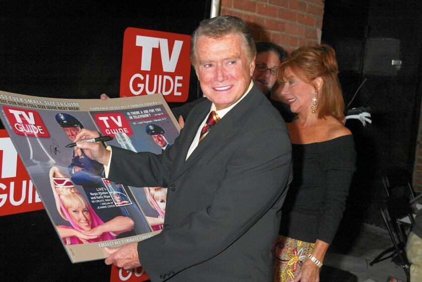"""Regis Philbin signs a large poster copy of his TV Guide cover in which he is dressed as Major Nelson from """"I Dream of Jeannie."""""""