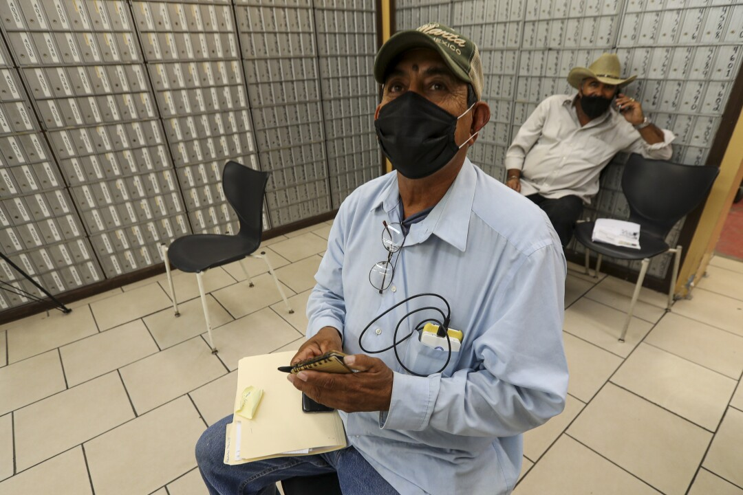 Fernando Fausto, 59, a resident of Mexicali, waits at a private service agency to file for unemployment in Calexico.