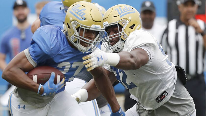 LOS ANGELES, CALIF. - APRIL 20, 2019. UCLA running back Jopshua Kelley tries to evade the grasp of