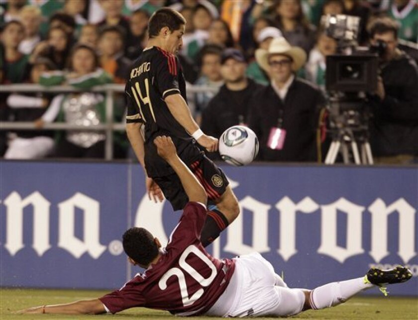 Mexico's Javier Hernandez, above, moves past Venezuela's Grenddy Perozo in the first half during an international friendly soccer game Tuesday, March 29, 2011, in San Diego. (AP Photo/Gregory Bull)