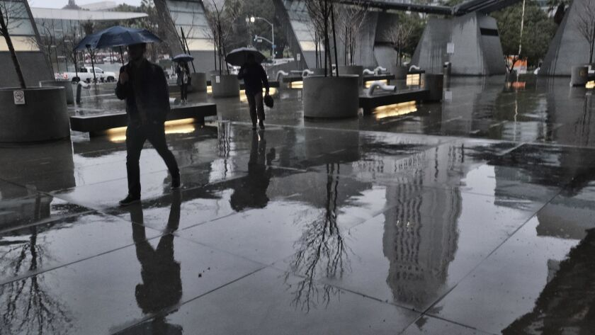 Los Angeles City Hall is reflected in the pavement as office workers arrive at the California Depart