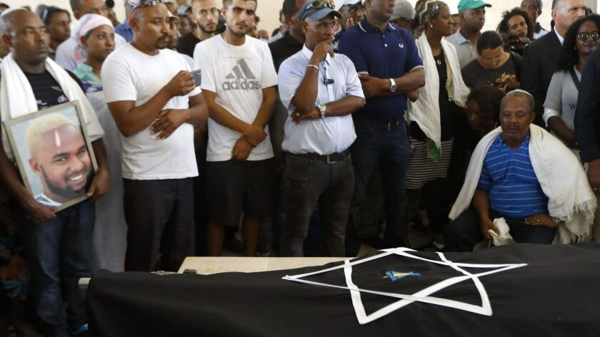 The father of Solomon Teka, an 18-year-old Israeli of Ethiopian descent who was killed by an off-duty Israeli police officer on Sunday, mourns over his son's body during his funeral in the Israeli coastal city of Haifa on Tuesday.