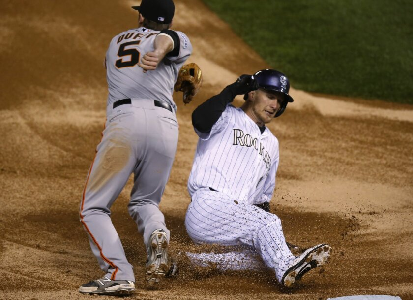 San Francisco Giants third baseman Matt Duffy, left, tries to field the throw as Colorado Rockies' Brandon Barnes slides safely into third base to advance on a single by pinch-hitter Michael McKenry in the bottom of the ninth inning of a baseball game Friday, May 22, 2015, in Denver. The Giants won 11-8. (AP Photo/David Zalubowski)