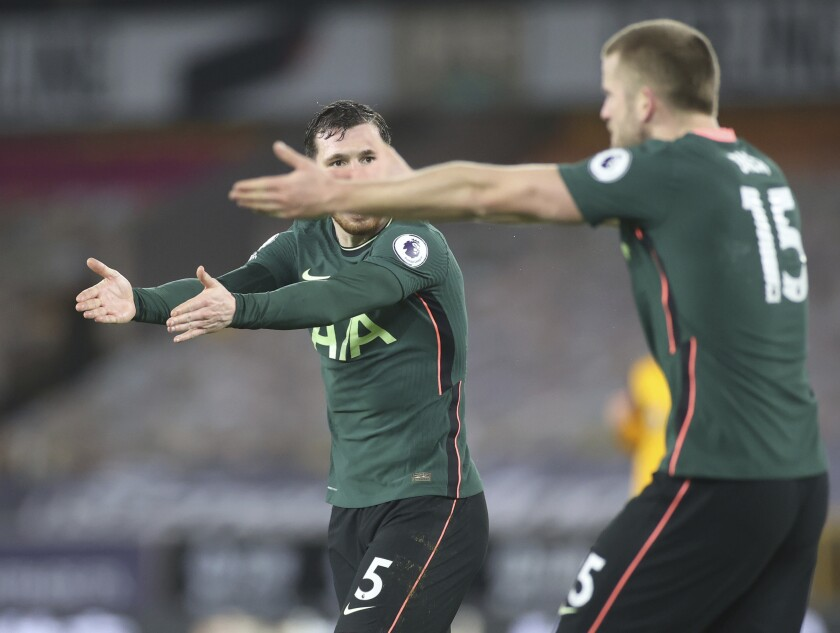 Tottenham's Eric Dier, right and Tottenham's Pierre-Emile Hojbjerg gesture to each other during the English Premier League soccer match between Wolverhampton Wanderers and Tottenham Hotspur at Molineux Stadium, in Woverhampton, England, Sunday, Dec. 27, 2020. (Carl Recine/ Pool via AP)