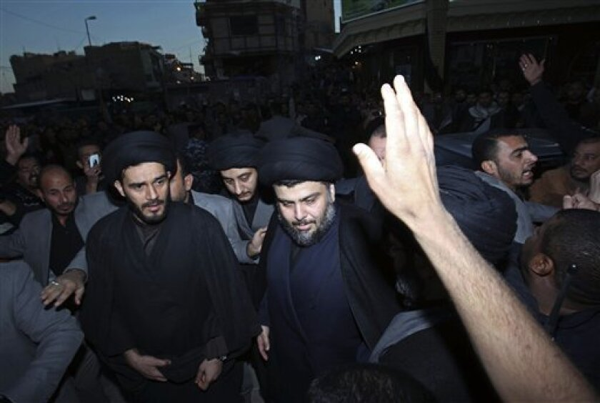 Anti-American cleric Muqtada al-Sadr, center, is surrounded by supporters in the Shiite city of Najaf, 160 kilometers (100 miles) south of Baghdad, Iraq, Wednesday, Jan. 5, 2011. Al-Sadr, who led several Shiite uprisings against American forces in Iraq before going into exile in neighboring Iran almost four years ago, has returned to Iraq, officials said Wednesday. (AP Photo/Alaa al-Marjani)