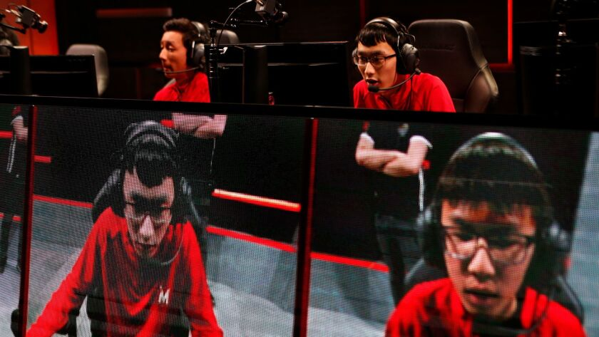 "Li-Yun Kwan, left, and Zhisheng Xue, members of the ""League of Legends"" team from the University of Maryland, participate in a championship match."