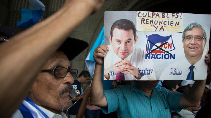 A demonstrator holds images of Guatemala's President Jimmy Morales, left, and his Vice President Jaf