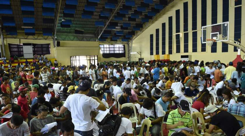 Drug users and dealers filling out forms on July 18 after voluntarily surrendering to local authorities in Tanauan town, Batangas province, south of Manila.