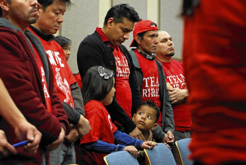Victor Lopez, center, bows his head during the opening prayer of the Irwindale City Council meeting Wednesday. Lopez, with his children Elsy, 10, and Joseph, 6, joined other Huy Fong Foods employees and supporters of the Sriracha hot sauce maker at a public hearing to discuss efforts to shut down the plant.
