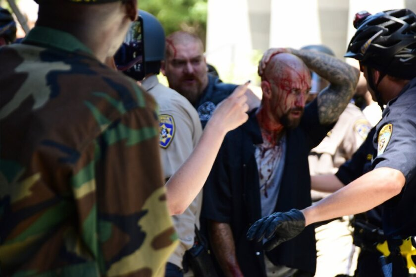 Police escort a wounded man away from the Capitol in Sacramento after a clash between far-right groups and counter-protesters turned violent in June 2016.