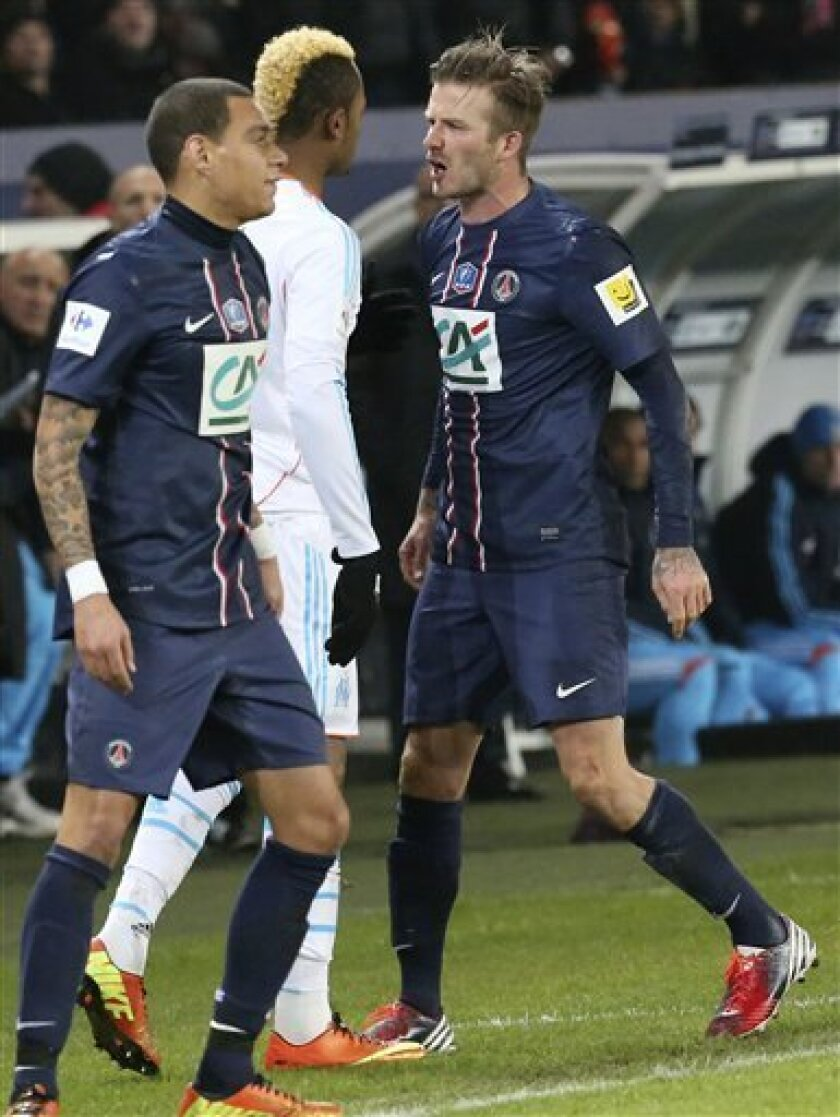 Paris Saint-Germain's David Beckham, right, reacts with Marseille's Jordan Ayew, left, after being fouled during the last 16 of a French Cup soccer match, at Parc des Princes stadium, in Paris, Wednesday, Feb. 27, 2013. Paris Saint Germain won 2-0. (AP Photo/Michel Euler)