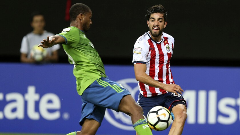 Rodolfo Pizarro of Chivas, right, fights for the ball with Jordan McCrary of Seattle Sounders Sounde