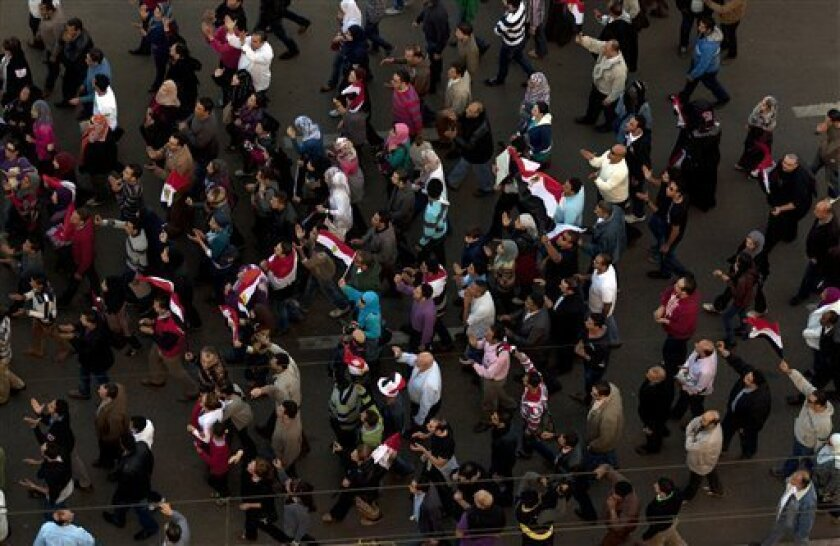 Egyptian protesters chant slogans against President Mohammed Morsi while marching to join their fellow protesters near the presidential palace, in Cairo, Egypt, Friday, Dec. 7, 2012. Egypt's political crisis spiraled deeper into bitterness and recrimination Friday as thousands of Islamist backers of the president vowed vengeance at a funeral for men killed in bloody clashes earlier this week and large crowds of the president's opponents marched on his palace to increase pressure after he rejected their demands. (AP Photo/Nasser Nasser)