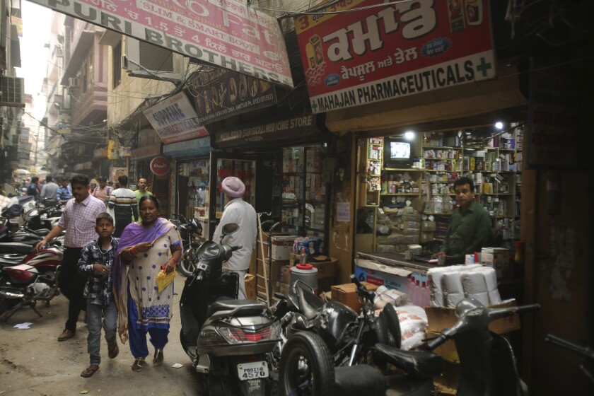 People walk past drugstores where tramadol was once easily accessible in Amritsar, in the northern Indian state of Punjab.