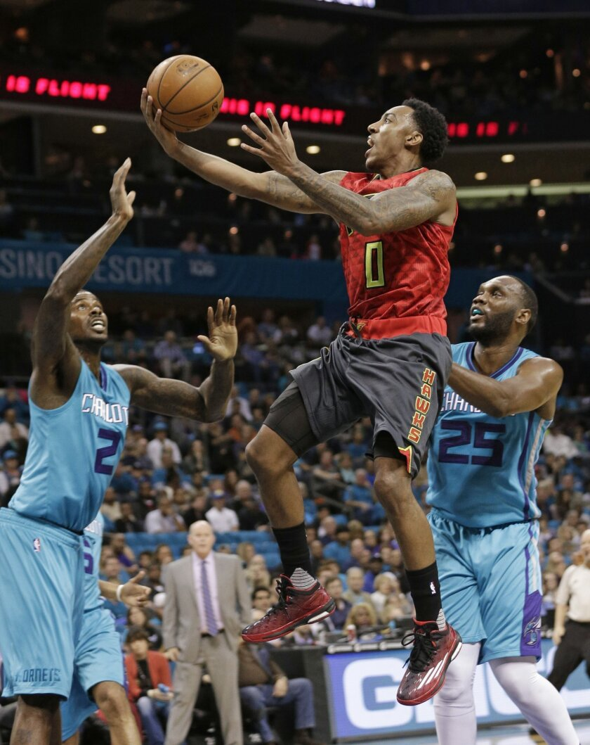Atlanta Hawks' Jeff Teague (0) drives past Charlotte Hornets' Al Jefferson (25) and Marvin Williams (2) in the first half of an NBA basketball game in Charlotte, N.C., Sunday, Nov. 1, 2015. (AP Photo/Chuck Burton)