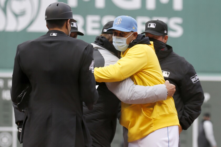 Boston Red Sox manager Alex Cora, front right, hugs Chicago White Sox manager Tony La Russa as the exchange lineups before a baseball game, Saturday, April 17, 2021, in Boston. (AP Photo/Mary Schwalm)