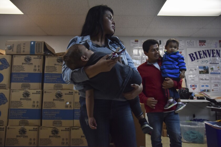 Immigrant parents hold their children at Catholic Charities of the Rio Grande Valley on Thursday, in McAllen, Texas. President Donald Trump ended family separations at the Mexican border but the U.S. government has done little to help with the reunifications, attorneys say.