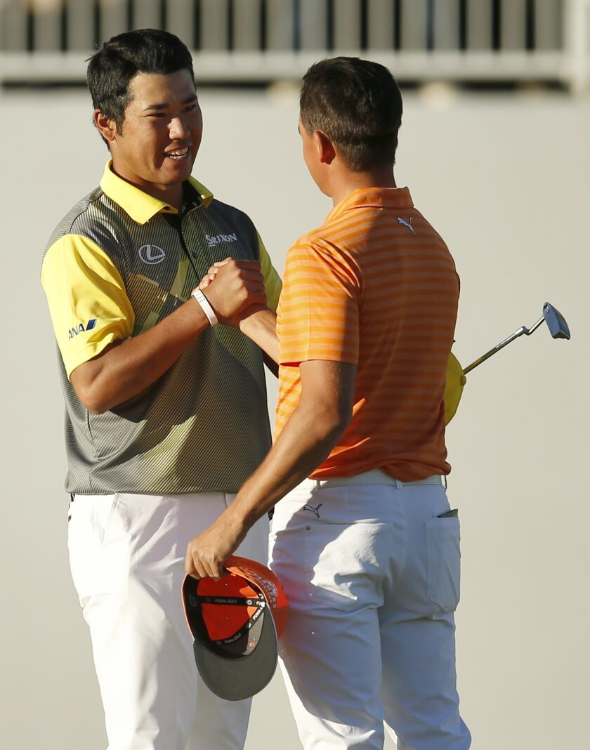 Hideki Matsuyama, left, shakes hands with Rickie Fowler after defeating Fowler in a 4-hole sudden death playoff and winning the Phoenix Open golf tournament, Sunday, Feb. 7, 2016, in Scottsdale, Ariz. (AP Photo/Rick Scuteri)
