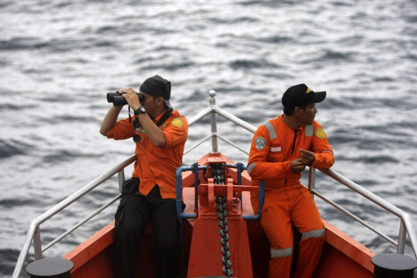 Indonesian search-and-rescue personnel keep a lookout aboard a ship heading to the Andaman Sea as part of the hunt for the missing Malaysia Airlines jetliner.