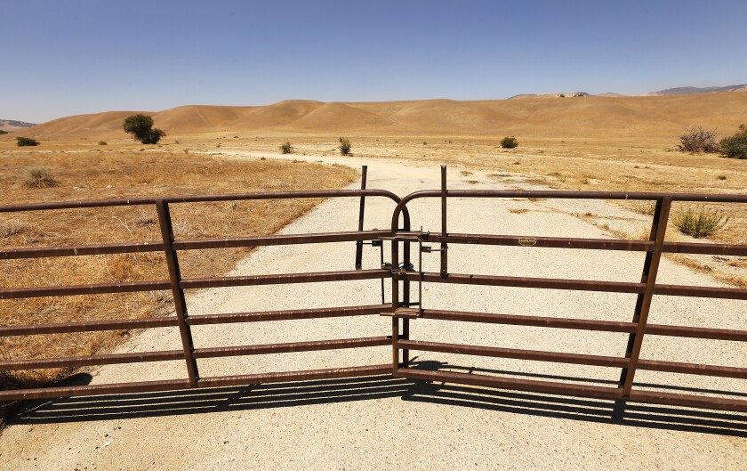 A gated dirt road in the sprawling grasslands of Tejon Ranch