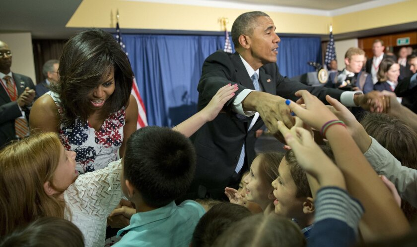 President Barack Obama and first lady Michelle Obama greet children and families of U.S. embassy personnel during an event at the Melia Habana Hotel in Havana, Cuba, Sunday, March 20, 2016. Obama's trip is a crowning moment in his and Cuban President Raul Castro's ambitious effort to restore normal relations between their countries. (AP Photo/Pablo Martinez Monsivais)