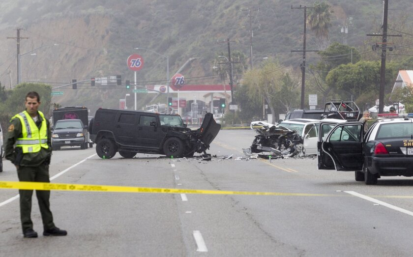 A Los Angeles County Sheriff's deputy guards the scene on Corral Canyon Road in Malibu. One person was killed and five were injured in the crash.
