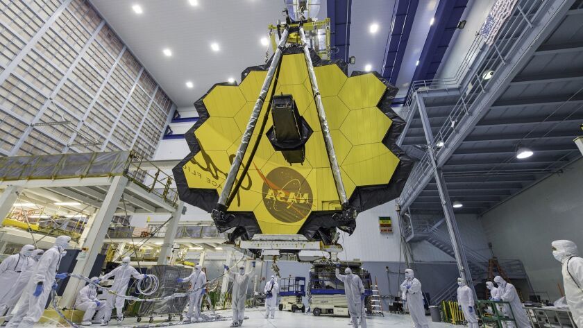 In this April 13, 2017 photo provided by NASA, technicians lift the mirror of the James Webb Space T