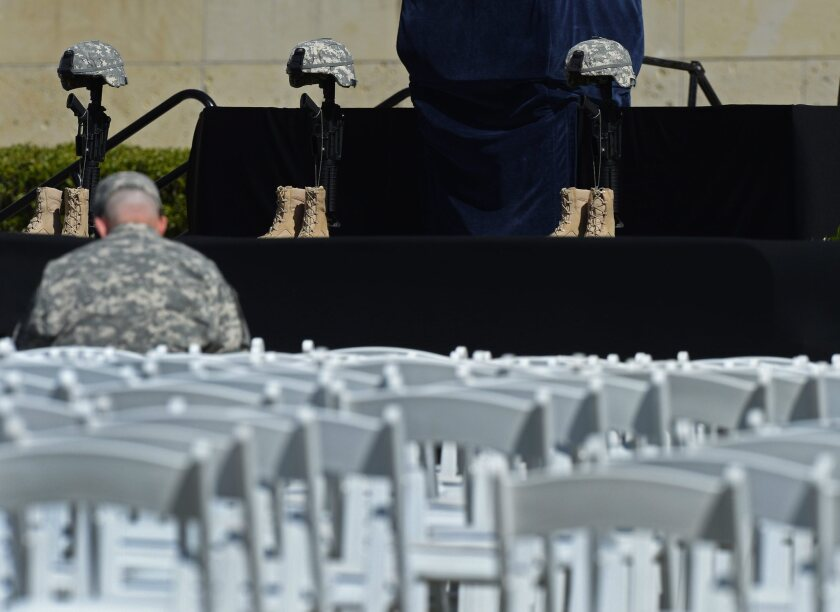 A soldier sits in front of the memorial representing the three troops killed in a shooting rampage last week at Ft. Hood in Texas. A memorial service will be held on the base Wednesday.