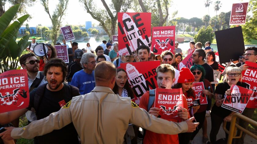 A rally in front of an L.A. County Sheriff's Department patrol station in July protests the agency's cooperation with immigration officers and voices support for a state bill that would restrict how law enforcement officials share information with federal immigration officers.