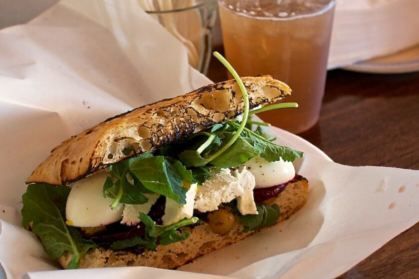 A sandwich of beets and eggs comes between halves of ciabatta bread.