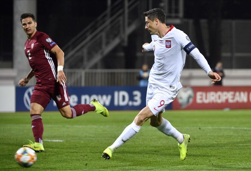 FILE - In this Thursday, Oct. 10, 2019 filer, Poland's Robert Lewandowski scores his first goal during Euro 2020 group G qualifying soccer match between Latvia and Poland in Riga, Latvia. (AP Photo/Roman Koksarov, File)