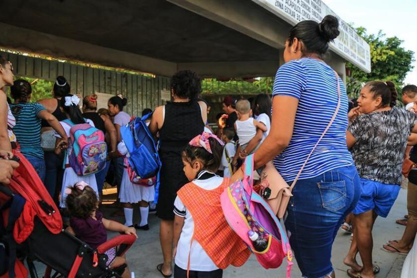 Menores acompañados de sus madres son vistos hoy, lunes 20 de agosto de 2018, durante el inicio del ciclo escolar, en la ciudad de Acapulco (México). EFE