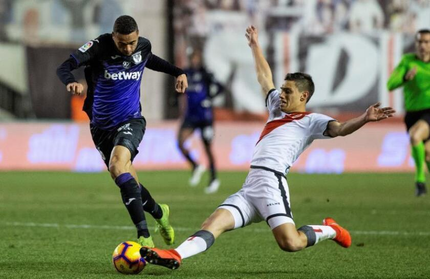 El delantero marroquí del Leganés Youssef En-Nesyri (i) pelea un balón con el defensa uruguayo del Rayo Vallecano Emiliano Velázquez durante el partido de La Liga que se disputa en el estadio de Vallecas en Madrid . EFE / Rodrigo Jimenez