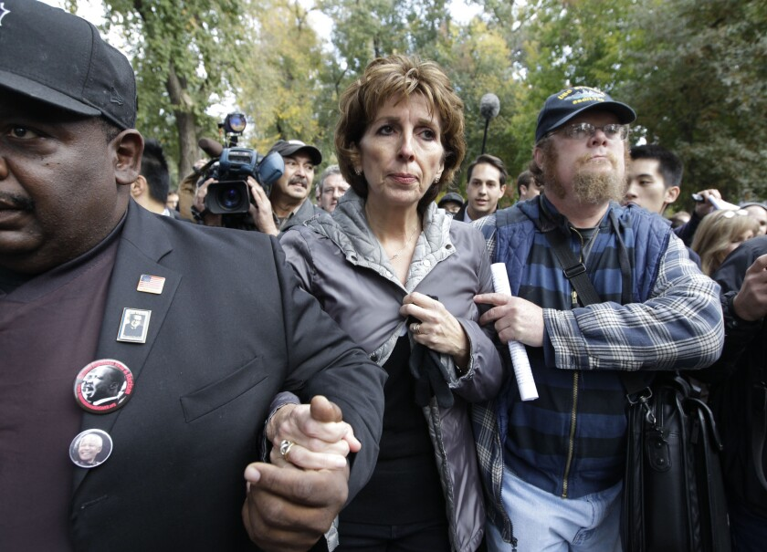 UC Davis Chancellor Linda Katehi is escorted from the stage after speaking about the pepper-spraying incident on campus in 2011.