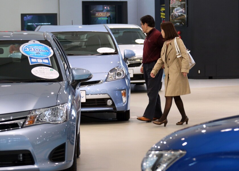 Visitors look at a Toyota Motor Corp. vehicle at the company's showroom in Tokyo, Japan. Toyota called back more than 6 million vehicles to fix a range of safety defects in one of the biggest recalls in automotive history.
