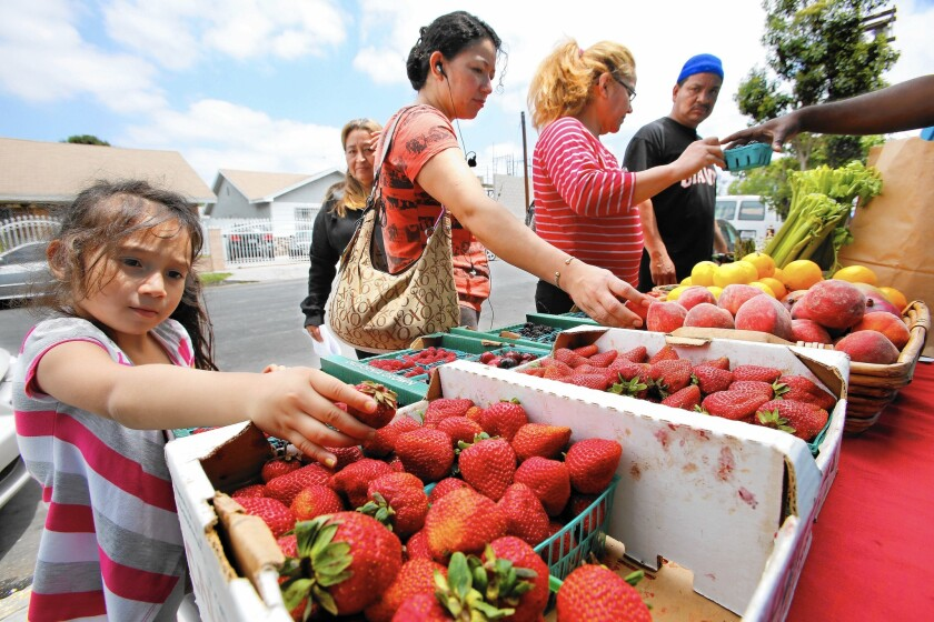 Belynda Umanzor, 3, left, and her mother Mily, 34, second from left, look at fruit at a produce stand in South Los Angeles.