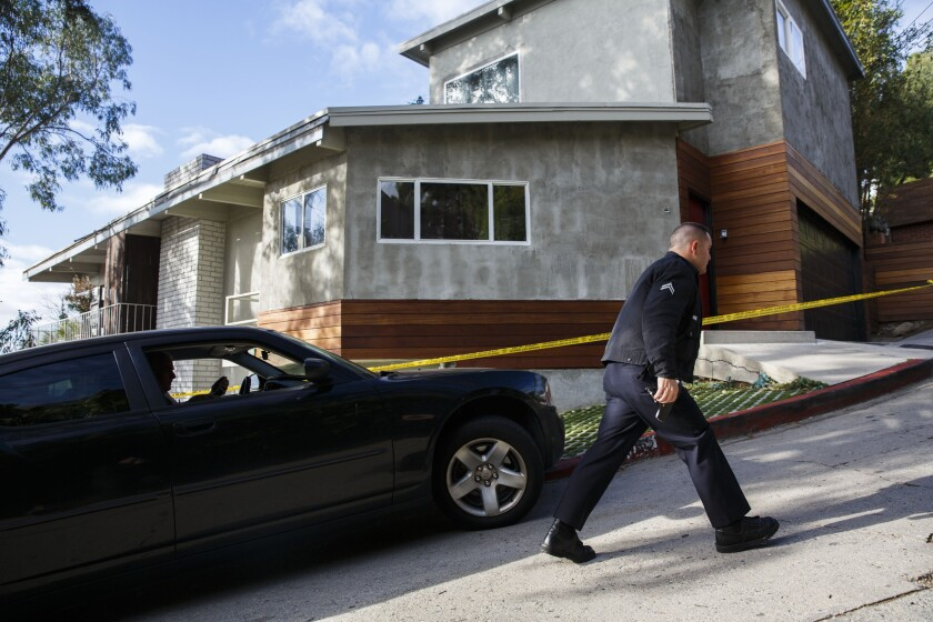 L.A. police officers wait for a search warrant outside of a home during a fatal shooting investigation in Hollywood Hills on Monday. Police say 27-year-old Henry Estrada was shot dead just after 8:30 p.m. Sunday at a residence in the 2000 block of Sycamore Avenue.