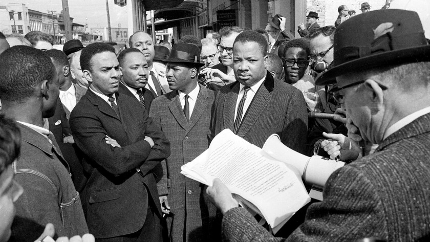 Andrew Young, left, arms crossed, with the Rev. Martin Luther King Jr.