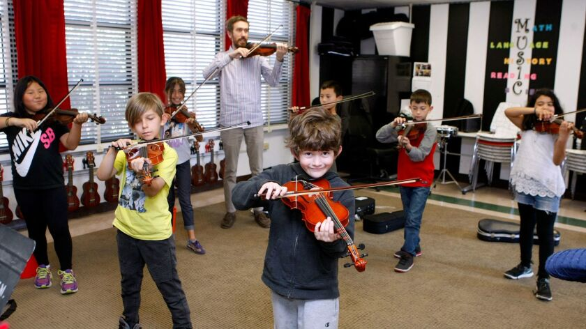 Roosevelt Elementary School music teacher Jacob Boyd poses with his violin class at the Burbank scho