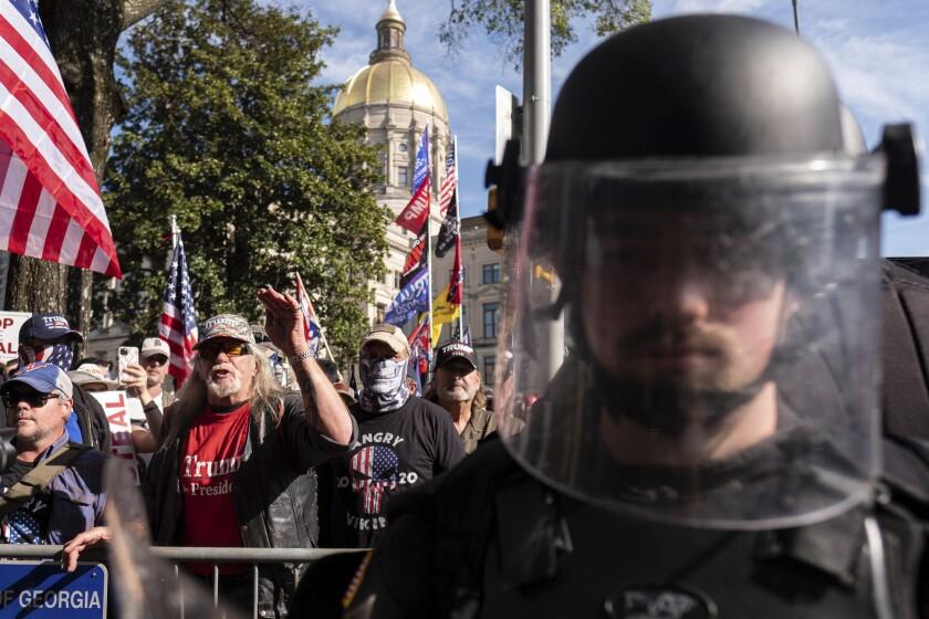 Un agente antidisturbios monta guardia interponiéndose entre partidarios del presidente Donald Trump y contramanifestantes