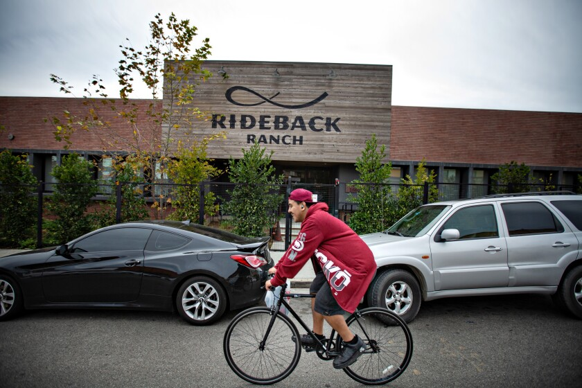 A cyclist passes Rideback Ranch, a communal workspace in Los Angeles.