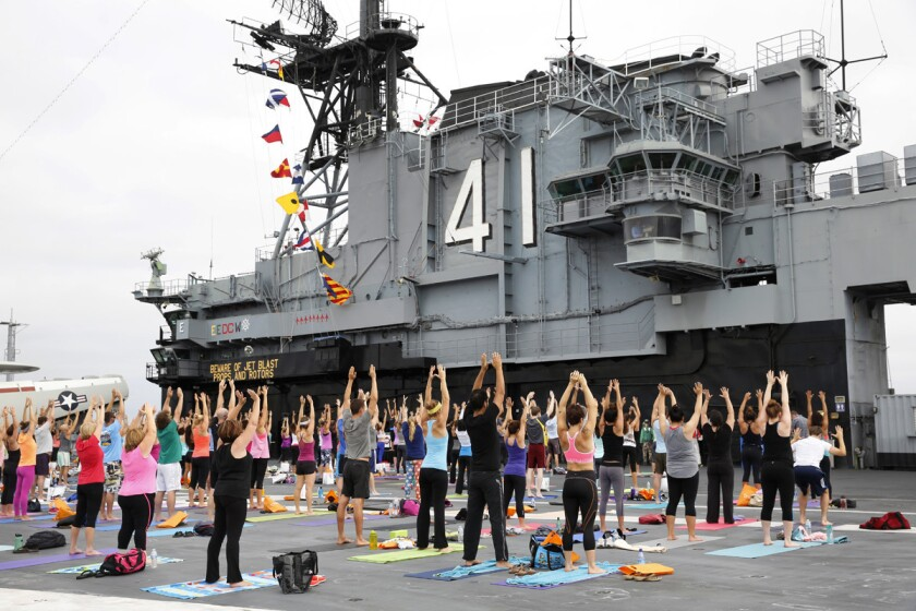 Participants stretch during an hour-long free yoga class on the flight deck of the USS Midway in 2014. (Nancee E. Lewis)