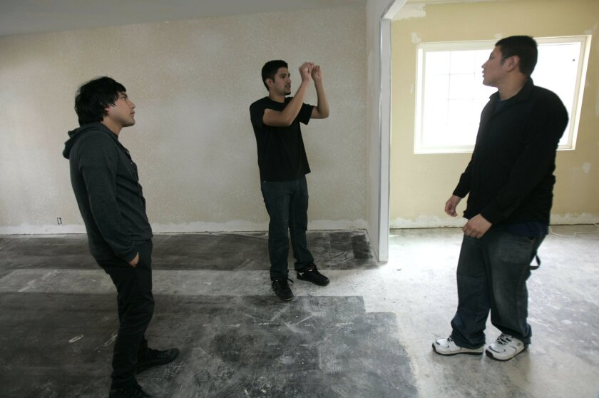 Jose Robles, 24, (center) talks to his brothers Mario (right)and Juan about what will be done in their new home during renovation. The three brothers live in the garage while their home is being renovated.