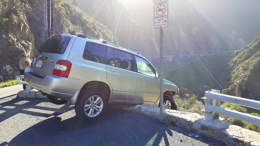 A driver who managed to escape this SUV teetering on the edge of Malibu Canyon Road was then struck by a passing tour bus.