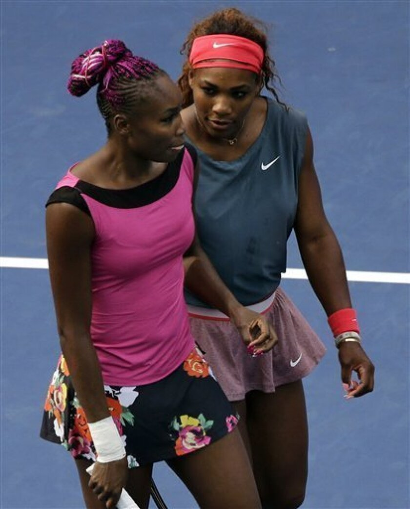 Venus, left, and Serena Williams talk between points during a doubles match against Raquel Kops-Jones and Abigail Spears, in the second round of the 2013 U.S. Open tennis tournament, Saturday, Aug. 31, 2013, in New York. (AP Photo/Mike Groll)