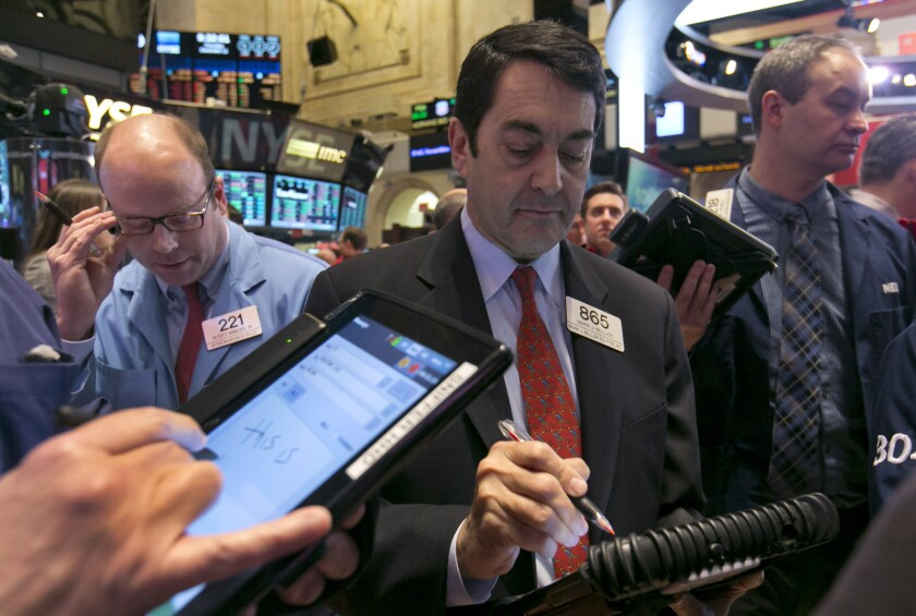 Mark Muller, center, works with fellow traders on the floor of the New York Stock Exchange Thursday. A strong report on retail sales pushed U.S. stocks higher in early trading Thursday.