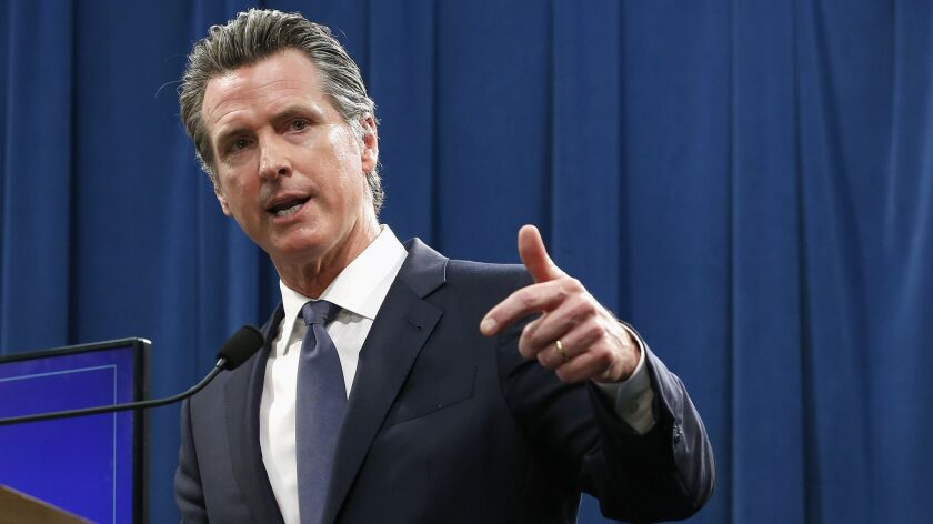 Gov. Gavin Newsom gestures as he speaks at a lectern